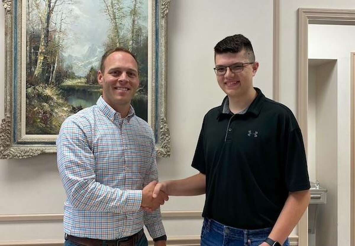 Farmers State Bank Vice President Bryan Hubbert presents a check to Justin Galloway.