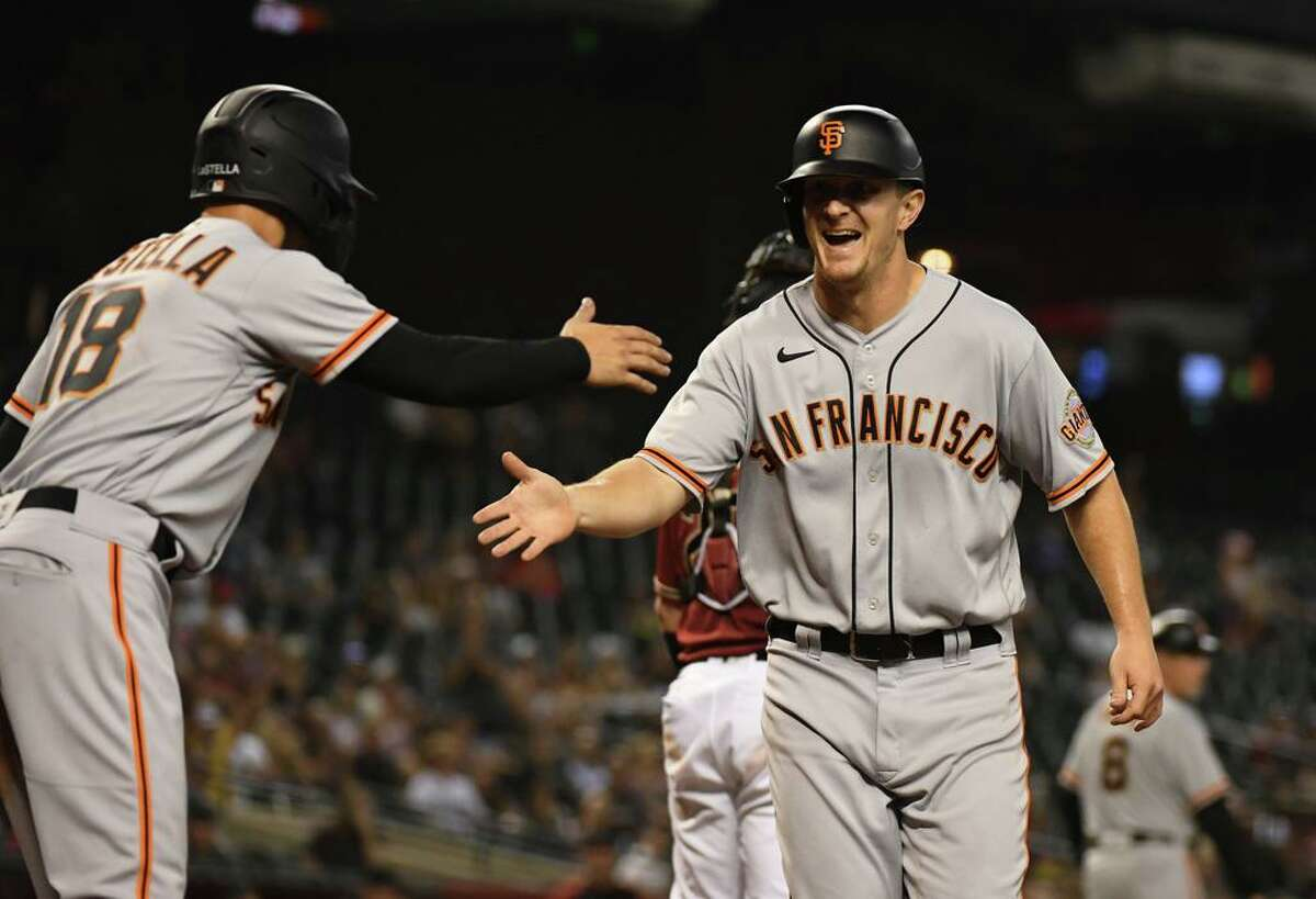 PHOENIX, ARIZONA - AUGUST 04: Alex Dickerson #12 of the San Francisco Giants celebrates with Tommy La Stella #18 after scoring on a two-run single off the bat of Donovan Solano against the Arizona Diamondbacks in the sixth inning at Chase Field on August 04, 2021 in Phoenix, Arizona. (Photo by Norm Hall/Getty Images)