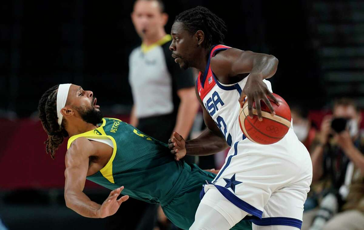 United States's Jrue Holiday (12), right, and Australia's Patty Mills (5) fight for the ball during men's basketball semifinal game at the 2020 Summer Olympics, Thursday, Aug. 5, 2021, in Saitama, Japan. (AP Photo/Eric Gay)