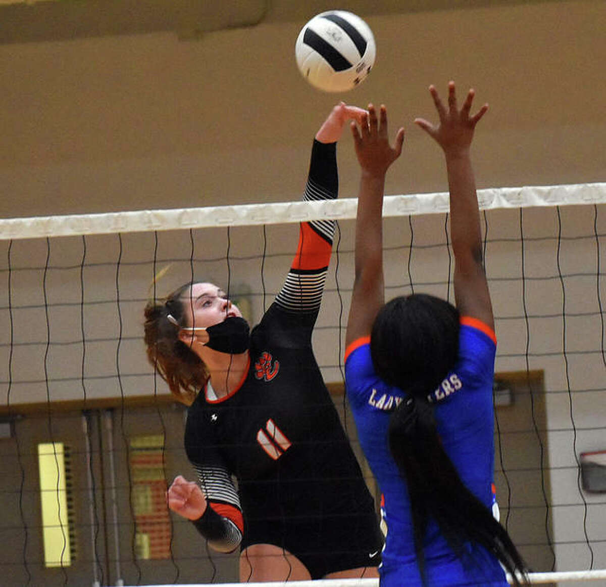 Edwardsville's Gabby Saye smashes a kill past an East St. Louis blocker during the first game in Edwardsville.