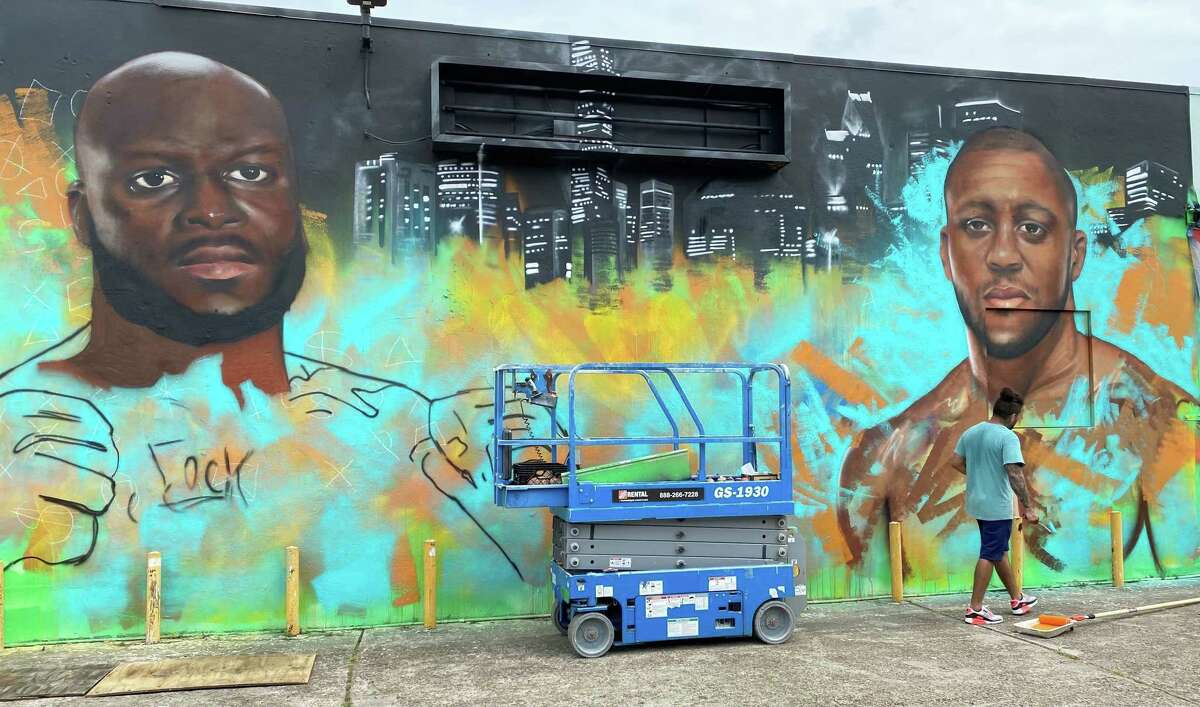Houston artist Franky Cardona works on a mural Wednesday, Aug. 4, 2021, promoting UFC 265's main event between Derrick Lewis and Ciryl Gane. The mural is located at 2102 Leeland Street.