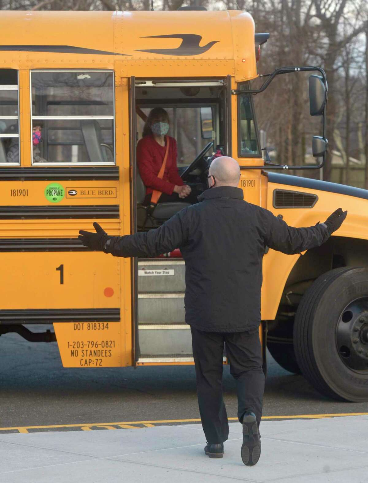 Stadley Rough Elementary School principal Lenny Cerlich welcomes students and their bus driver back to school for the first time since March of last year. Tuesday, January 19, 2021, in Danbury, Conn. Danbury is participating in a state program intended to better engage students who struggled during COVID-19.