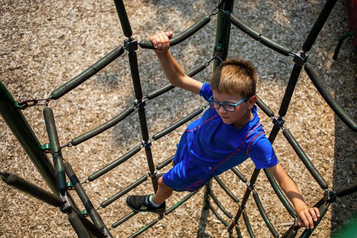 Levi Schulz, 7, climbs on playground equipment at Chippewassee Park Thursday, Aug. 5, 2021 in Midland. (Katy Kildee/kkildee@mdn.net)