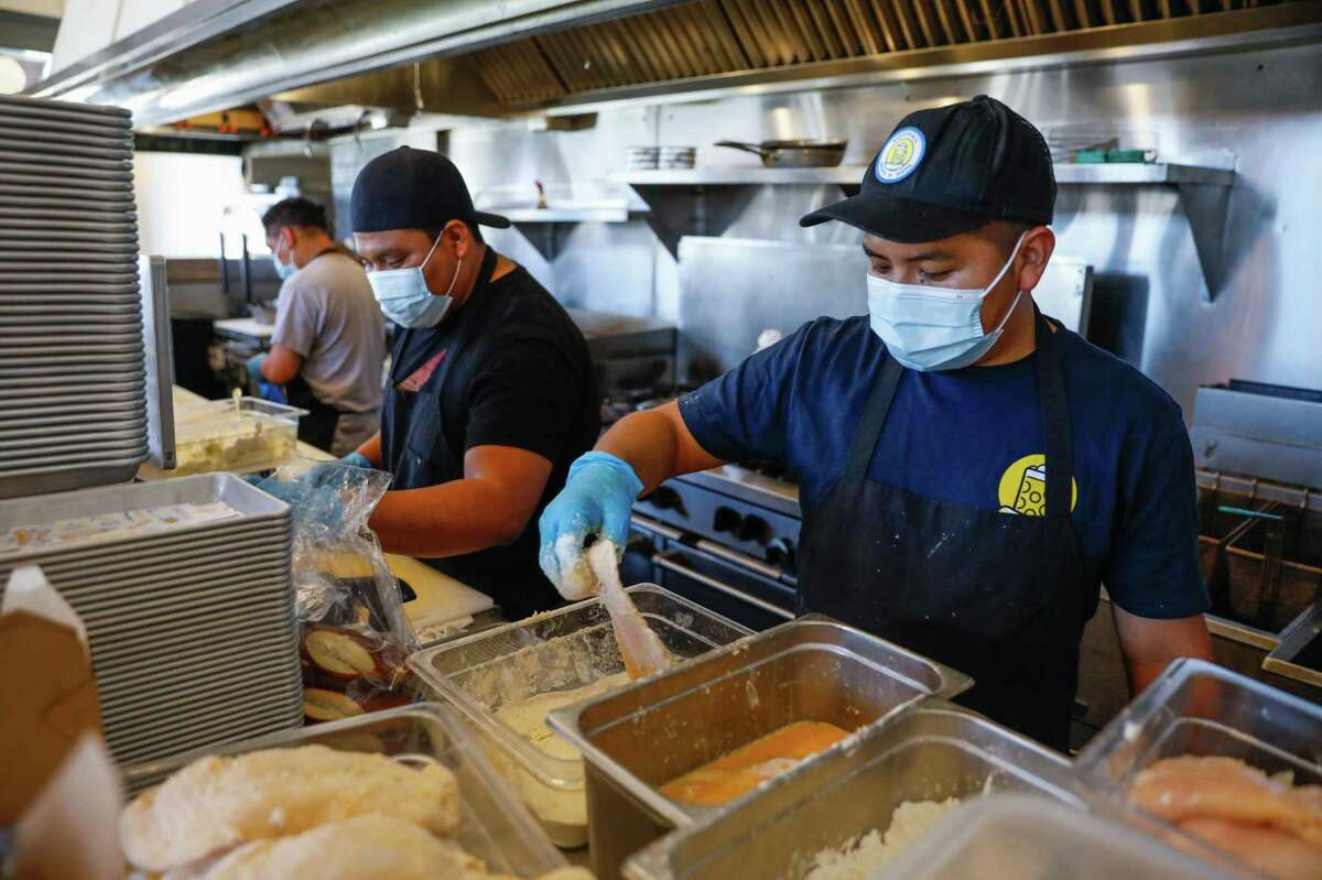 Prep cook Byron Chavix (right) wears a mask as he prepares for dinner service at Wursthall on Friday, July 16, 2021 in San Mateo, California.