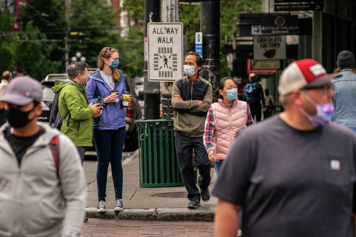 FILE - Pedestrians fill the sidewalk as Seattle has become the first major city to reach a 70 percent COVID-19 vaccination rate on June 10, 2021 in Seattle, Washington.