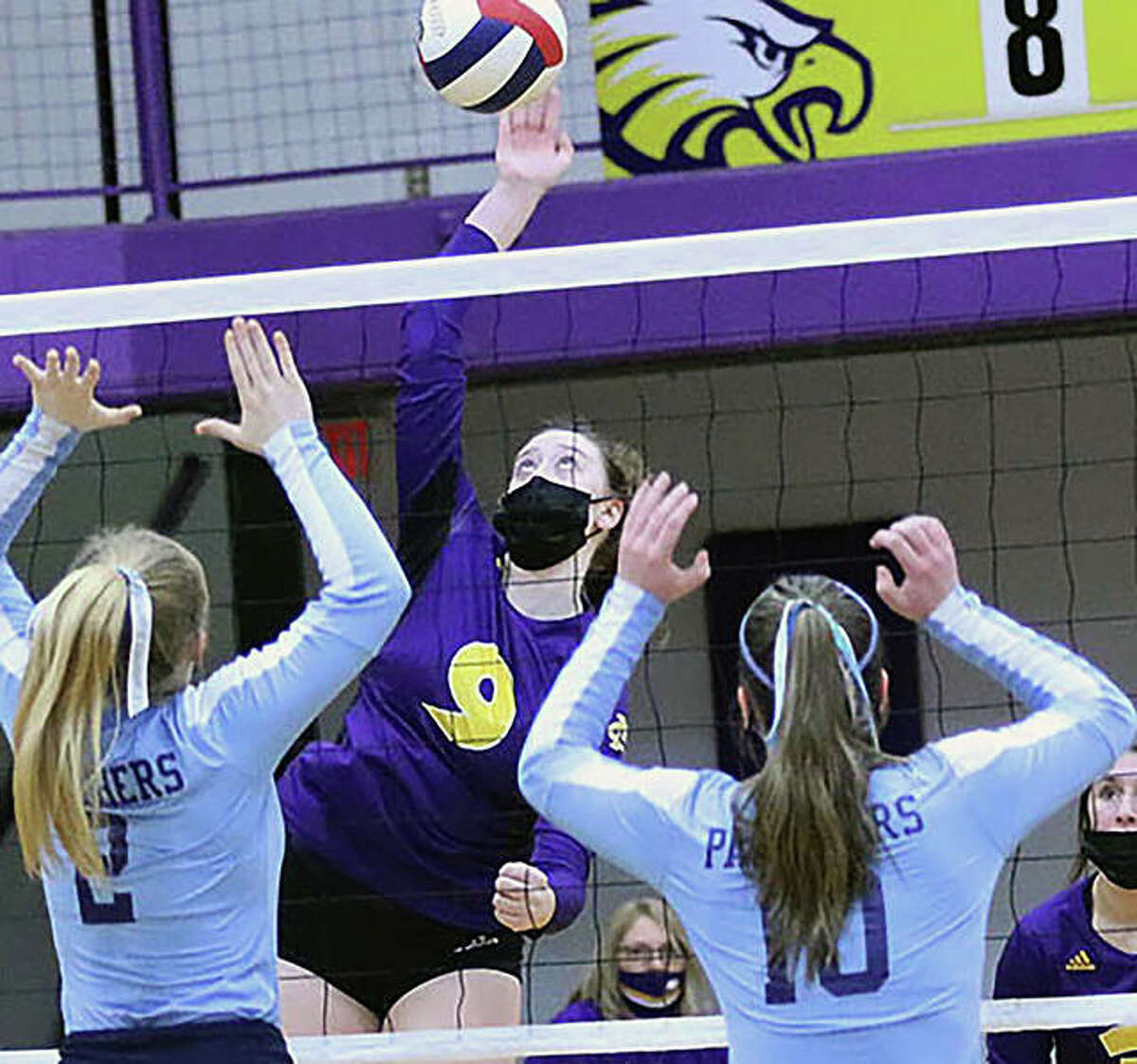CM's Lauren Dunlap (9) attacks before Jersey's Sally Hudson and Caroline Gibson (10) can put up a block in a March 18 volleyball match in Bethalto. Volleyball teams, as well as athletes playing other indoor fall sports, will be required to wear masks temporarily, according to the IHSA.