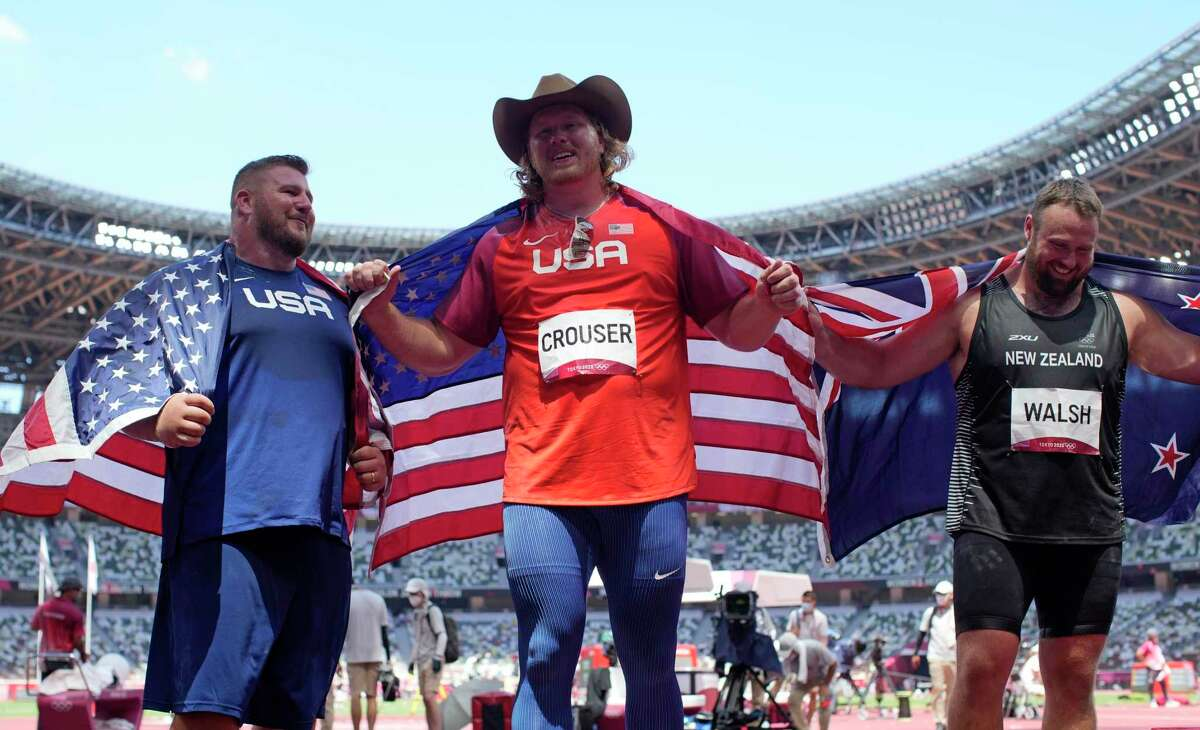 Ryan Crouser, of United States, center, celebrates after winning the gold in the final of the men's shot put with Joe Kovacs, of United States, left, silver, and Tomas Walsh, of New Zealand, bronze, at the 2020 Summer Olympics, Thursday, Aug. 5, 2021, in Tokyo, Japan. (AP Photo/Francisco Seco)