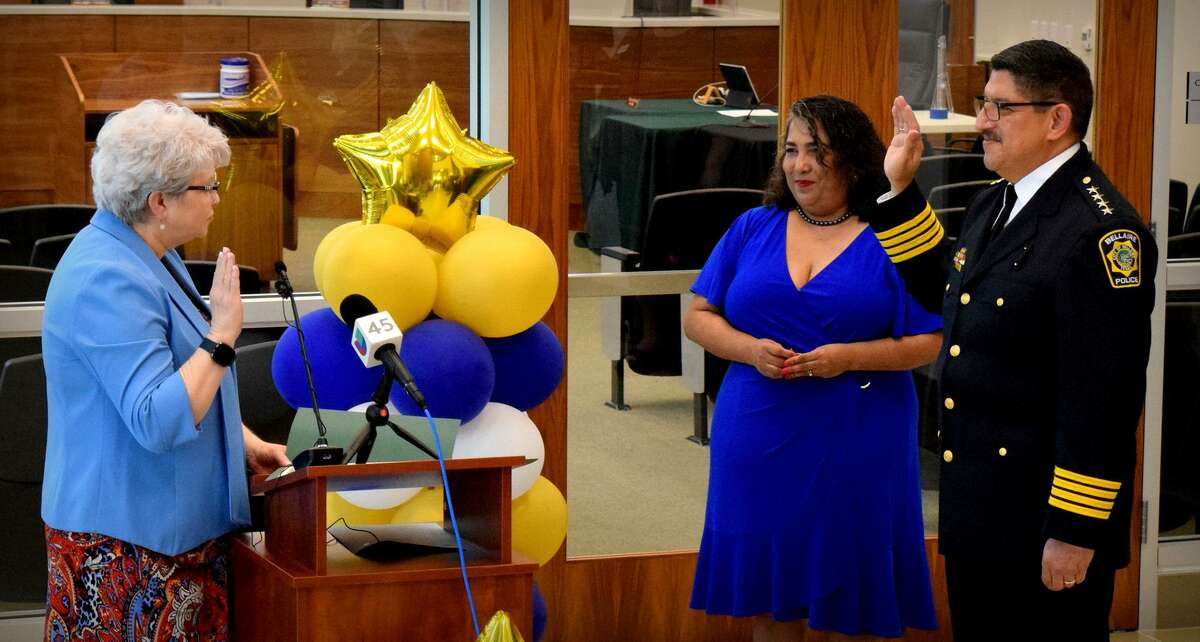 """Bellaire City Clerk Tracy Dutton administers the oath of office to new Chief of Police Onesimo """"Mo"""" Lopez Jr. at a ceremony on Aug. 2. Lopez's wife Faby stands next to him."""