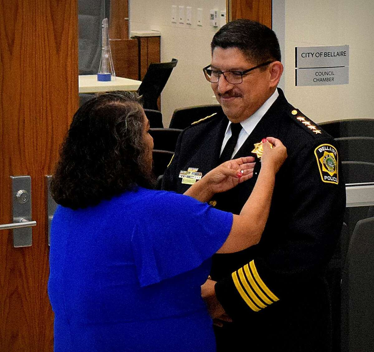 """Onesimo """"Mo"""" Lopez Jr.'s wife Faby pins the Chief's badge on him following his swearing in as the City of Bellaire's new Chief of Police at a ceremony on Aug. 2."""