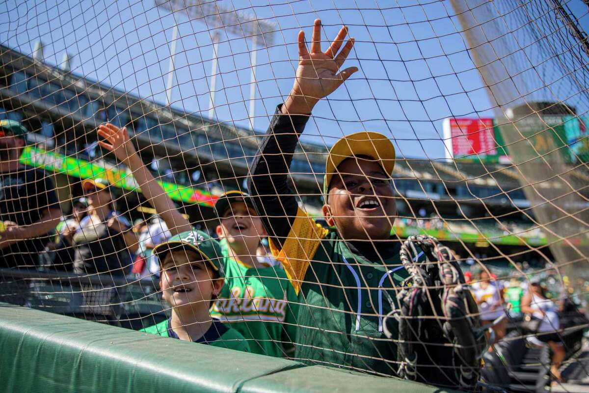 From left: Dillon Fischer, 7, Devon Fischer, 9, and Javaughn Thomas, 8, try to get the attention of Stomper, the Oakland Athletics?• mascot following the MLB game between the A?•s and the Los Angeles Angels at RingCentral Coliseum on Tuesday, July 20, 2021, in Oakland, Calif. The A?•s won 6-0.