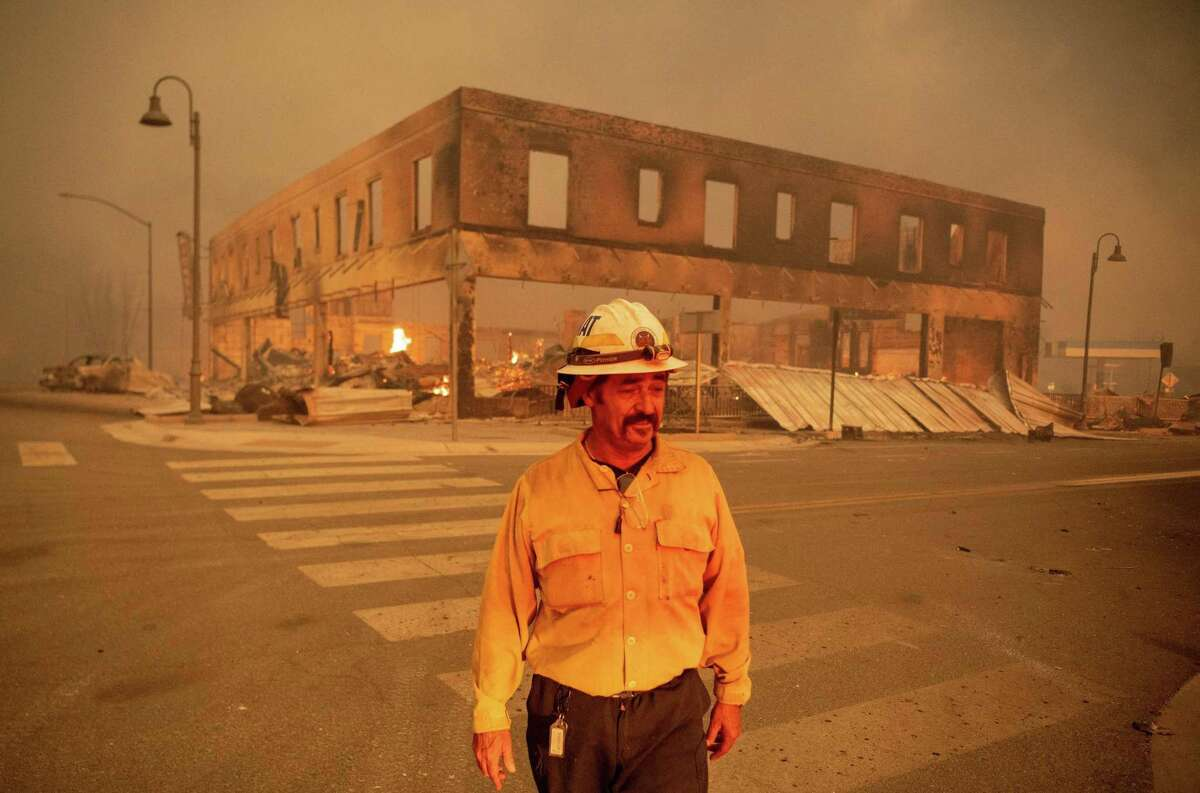 Battalion Chief Sergio Mora looks on as the Dixie Fire burns through downtown Greenville on Aug. 4.