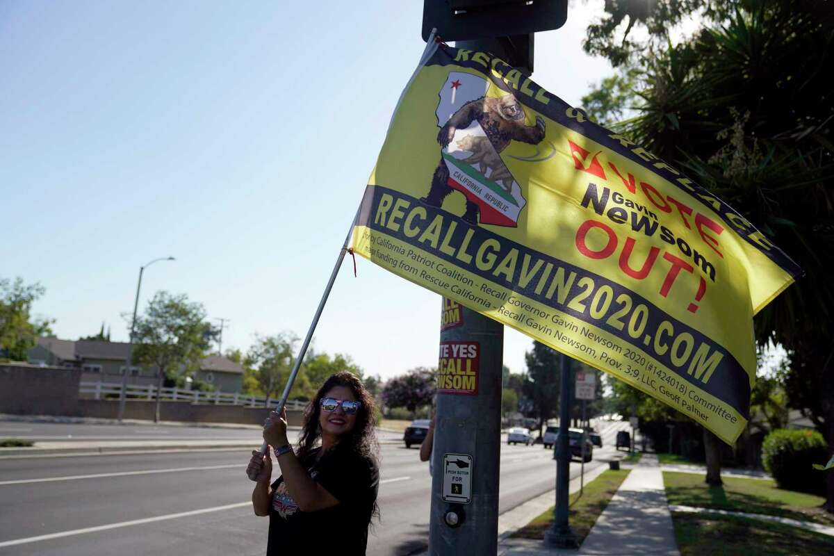 A supporter of the California recall of Gov. Gavin Newsom holds a sign outside of a debate by Republican gubernatorial candidates at the Richard Nixon Presidential Library on Wednesday.
