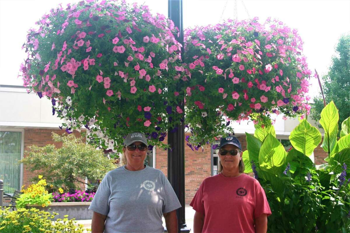 From left, Carla Wheeler and Leah Vander Sloot work together with the Big Rapids Parks Department to maintain and care for the flowers in the city. (Pioneer photo/Cathie Crew)