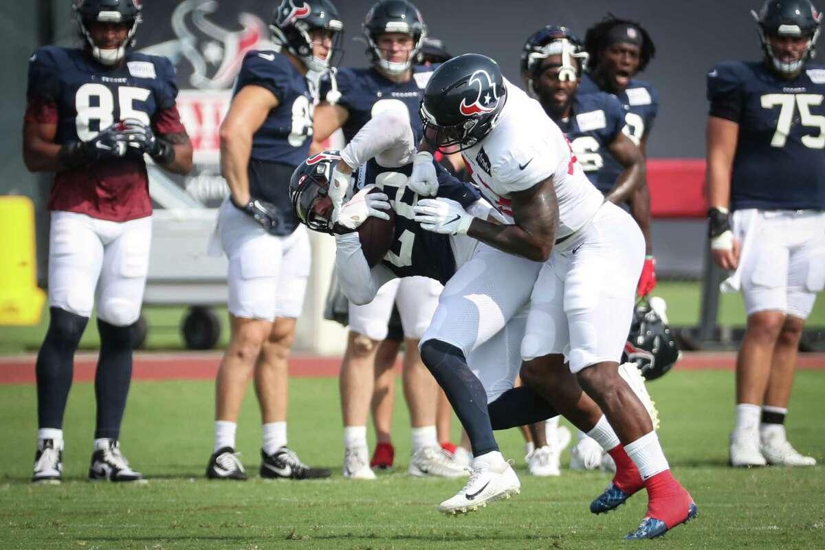Houston Texans linebacker Neville Hewitt (43) knocks down running back Rex Burkhead (28) during an NFL training camp football practice Thursday, Aug. 5, 2021, in Houston.