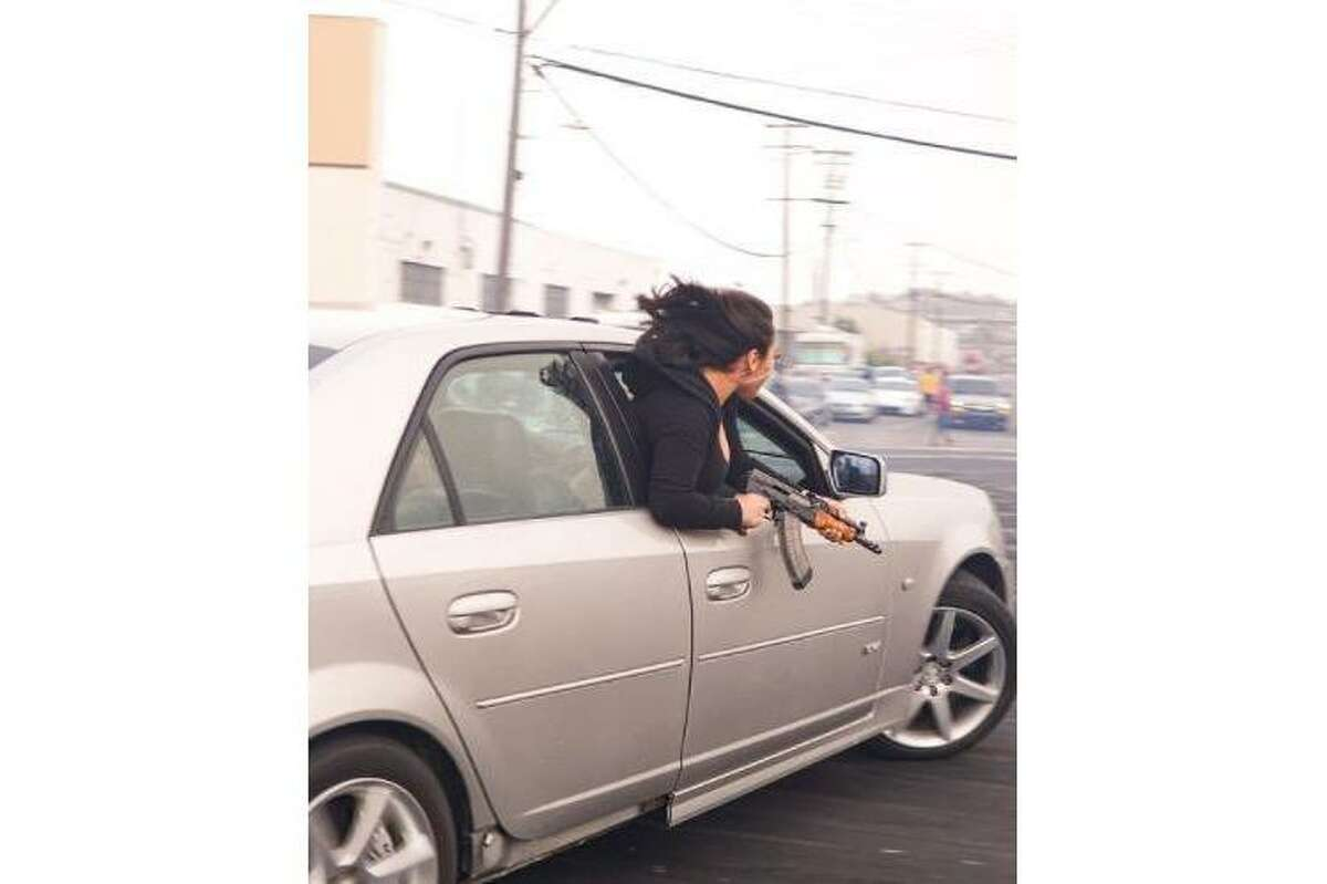 San Francisco police said this photo shared by the department on social media shows a woman holding an AK-47 while leaning out the window of a moving car July 11, 2021, at Barneveld and McKinnon avenues.