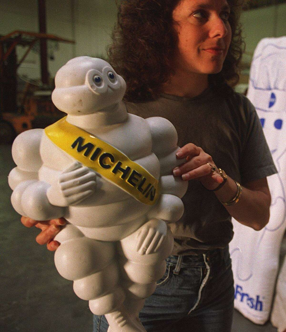 Ellen Weis holds a figurine of the Michelin Man at the Museum of Modern Mythology in San Francisco in 1996.