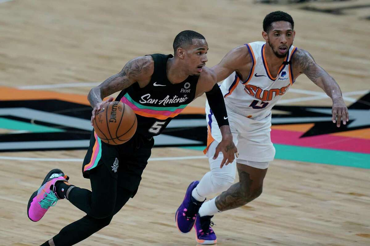 San Antonio Spurs guard Dejounte Murray (5) drives around Phoenix Suns guard Cameron Payne (15) during the second half of an NBA basketball game in San Antonio, Sunday, May 16, 2021. (AP Photo/Eric Gay)