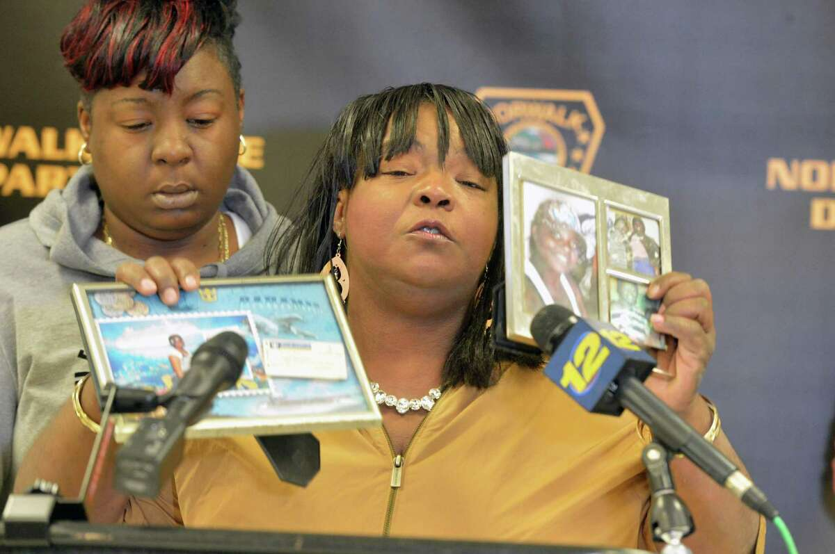 Barbara Smalls holds up photos of her granddaughter Rickita Smalls as she pleads for anyone having information about the August 6, 2011 murder of her and Iroquois Alston to please help, during at a press conference Monday November 13, 2017 at police headquarters in Norwalk Conn. to remind the public of a $50,000 reward leading to the arrest and conviction of the killer or killers.
