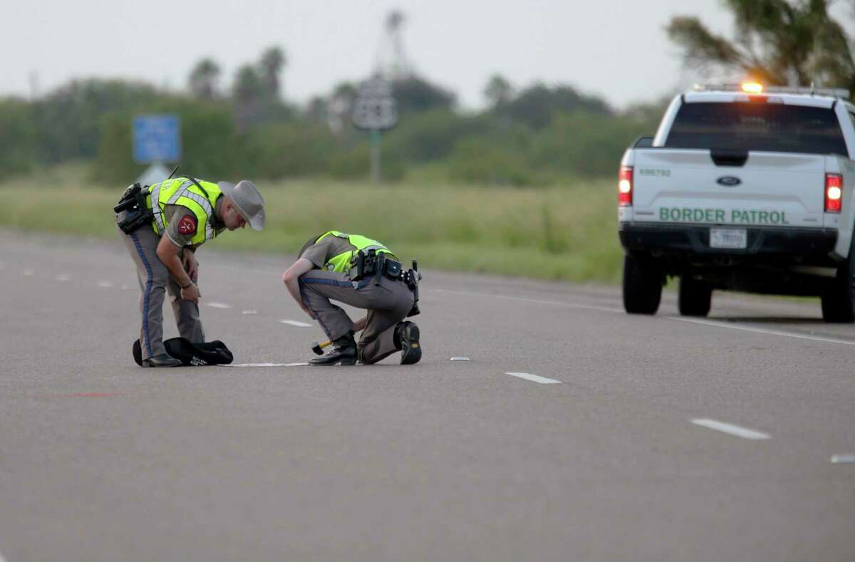 Texas Department of Public Safety survey the area where multiple people died after the van carrying migrants tipped over just south of the Brooks County community of Encino on Wednesday, Aug. 4, 2021, in Encino, Texas. The van crashed against a utility pole after it attempted to turn off of Highway 281 onto Business 281. Encino is about 2 miles (3.22 kilometers) south of the Falfurrias Border Patrol checkpoint. (Delcia Lopez/The Monitor via AP)