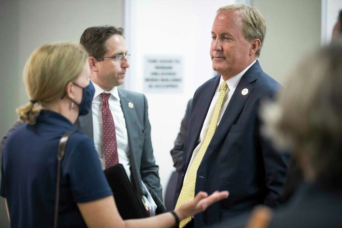 Texas Attorney General Ken Paxton talks to Suzanne Jarvis, of the Houston Recovery Center, about a proposed $26 billion multi-state opioid settlement during a news conference Thursday, Aug. 5, 2021 in Houston. Paxton encouraged cities and counties to sign on to the settlement agreement that could yield up to $1.5 billion for the state.
