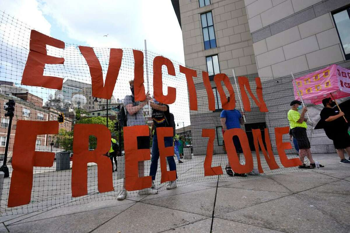 In this June 9, 2021, photo, people hold a sign during a rally in Boston protesting housing eviction. The Biden administration announced Thursday, July 29 it will allow a nationwide ban on evictions to expire Saturday, arguing that its hands are tied after the Supreme Court signaled it would only be extended until the end of the month.