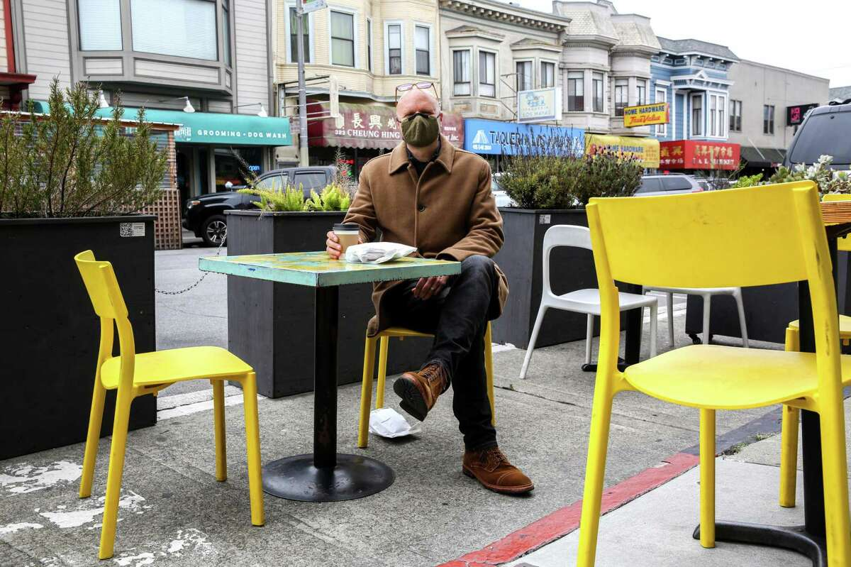 Tim Cordell, who is vaccinated, sits outside of a cafe in the Richmond District.