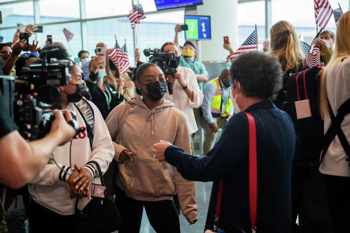 Olympic medalist Simone Biles approaches her mother Nellie Biles as the gymnast arrives to the George Bush Intercontinental Airport, Thursday, Aug. 5, 2021, in Houston. Biles won two Olympic medals during the Tokyo 2020 Olympics.