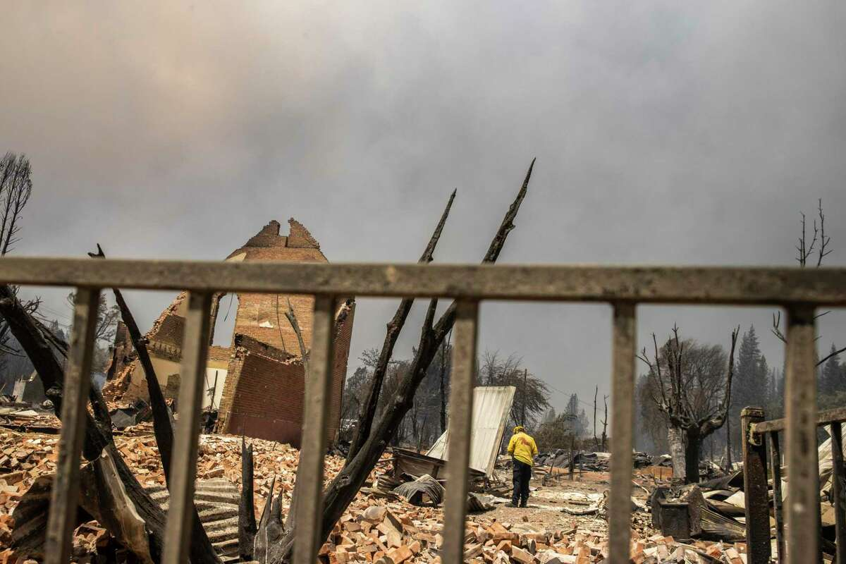 Jason Butcher, a forester with the Cal Fire Humboldt unit, performs a damage assessment on a property destroyed by the Dixie Fire in Greenville, California Thursday, Aug. 5, 2021.