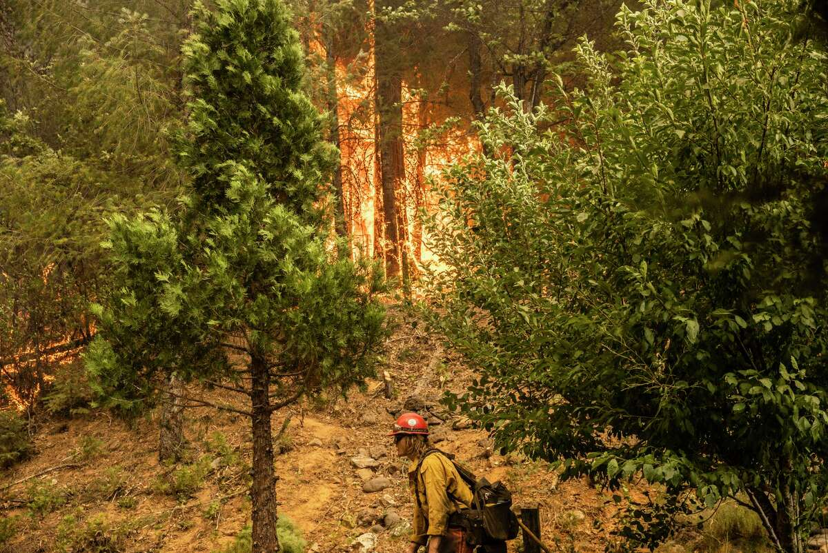 A firefighter with the Stanislaus Hotshots walks past a backfire while defending a home from the Dixie Fire in Greenville in the Sierra north of Lake Tahoe.