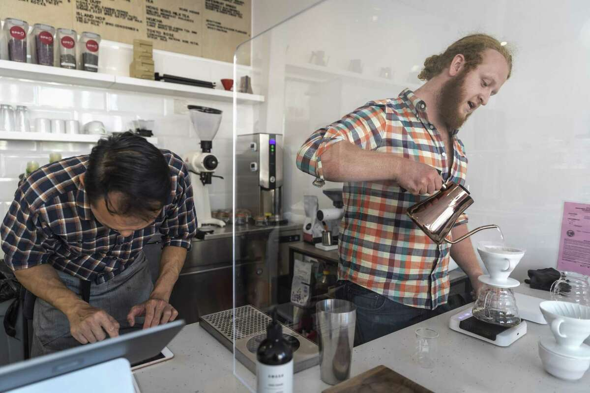Spro barista John Rider (right) prepares a pourover, measuring the rate at which hot water is added using a scale and iPad.