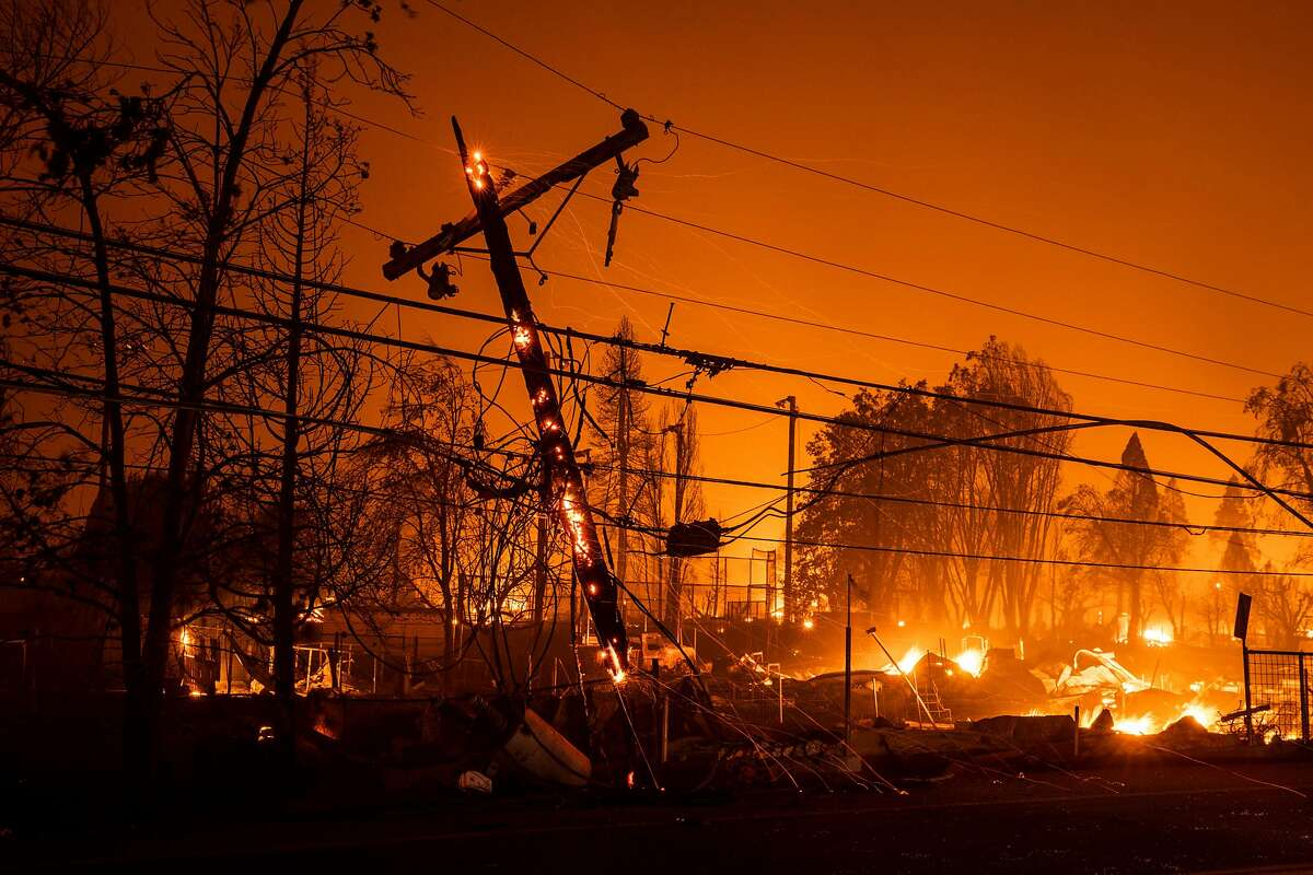 A utility pole smolders as properties burn nearby during the Dixie Fire in Greenville, California Wednesday, Aug. 4, 2021.