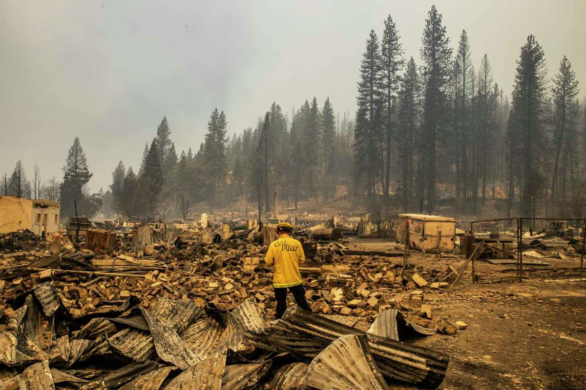A firefighter with Cal Fire San Mateo-Santa Cruz Unit performs a damage assessment on a property destroyed by the Dixie Fire in Greenville (Plumas County) on Aug. 5.