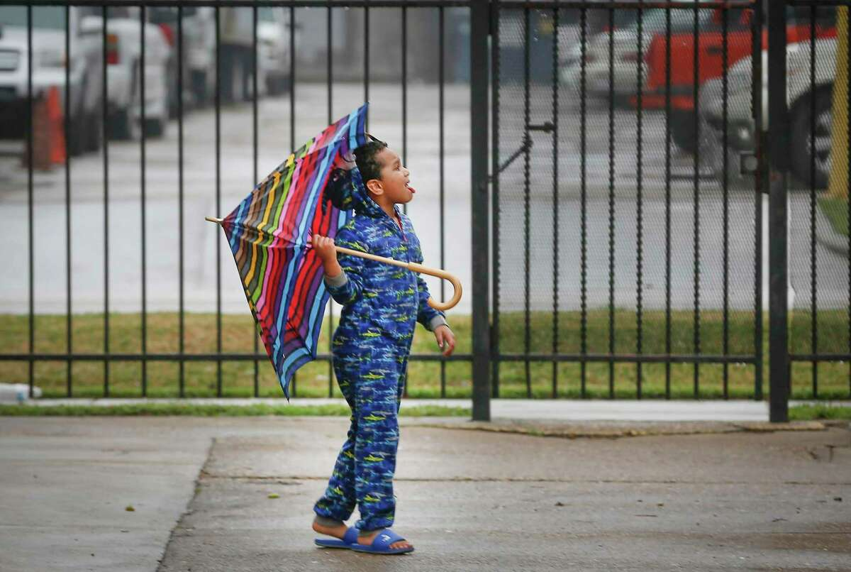 Johnny Gebremeskel, 6, catches rain on his tongue as light rain showers moved through the Ashford Buena Vista Apartments complex Wednesday, Feb. 10, 2021, in Houston.