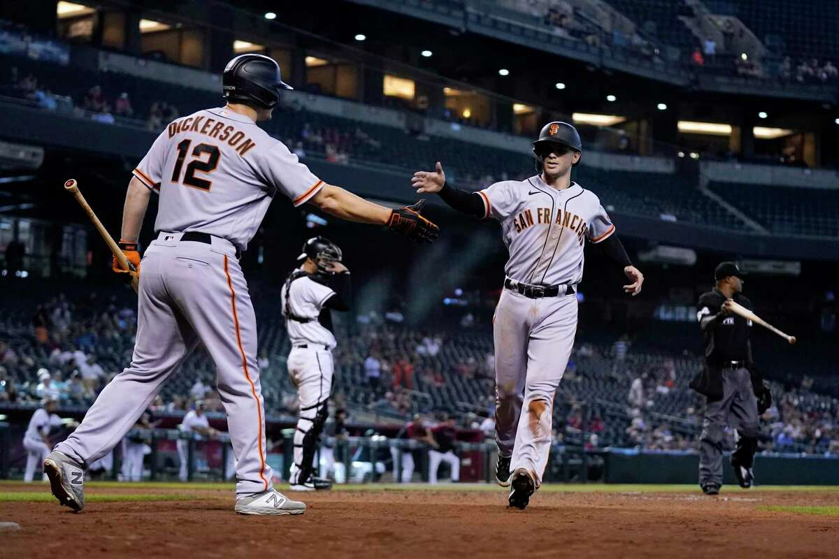 San Francisco Giants' Tommy La Stella, right, is congratulated by Alex Dickerson (12) after La Stella scored during the 10th inning of a baseball game against the Arizona Diamondbacks on Thursday, Aug. 5, 2021, in Phoenix. The Giants won 5-4. (AP Photo/Ross D. Franklin)