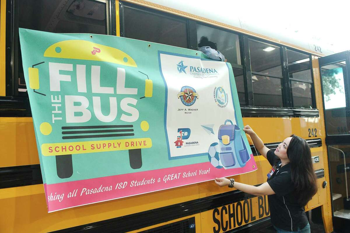 Rachel Rodriguez and Andrea Nguyen hang a banner on a Pasadena ISD School bus as they prepare for the drive.