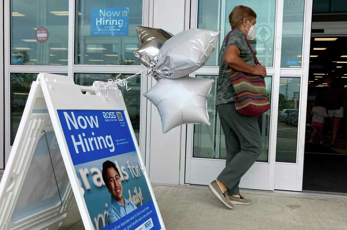 A shopper passes a hiring sign while entering a retail store in Morton Grove, Ill., Wednesday, July 21, 2021. Despite an uptick in COVID-19 cases and a shortage of available workers, the U.S. economy likely enjoyed a burst of job growth last month as it bounces back with surprising vigor from last year's coronavirus shutdown. The Labor Department's July jobs report Friday, Aug. 6 is expected to show that the United States added more than 860,000 jobs in July, topping June's 850,000, according to a survey of economists by the data firm FactSet.