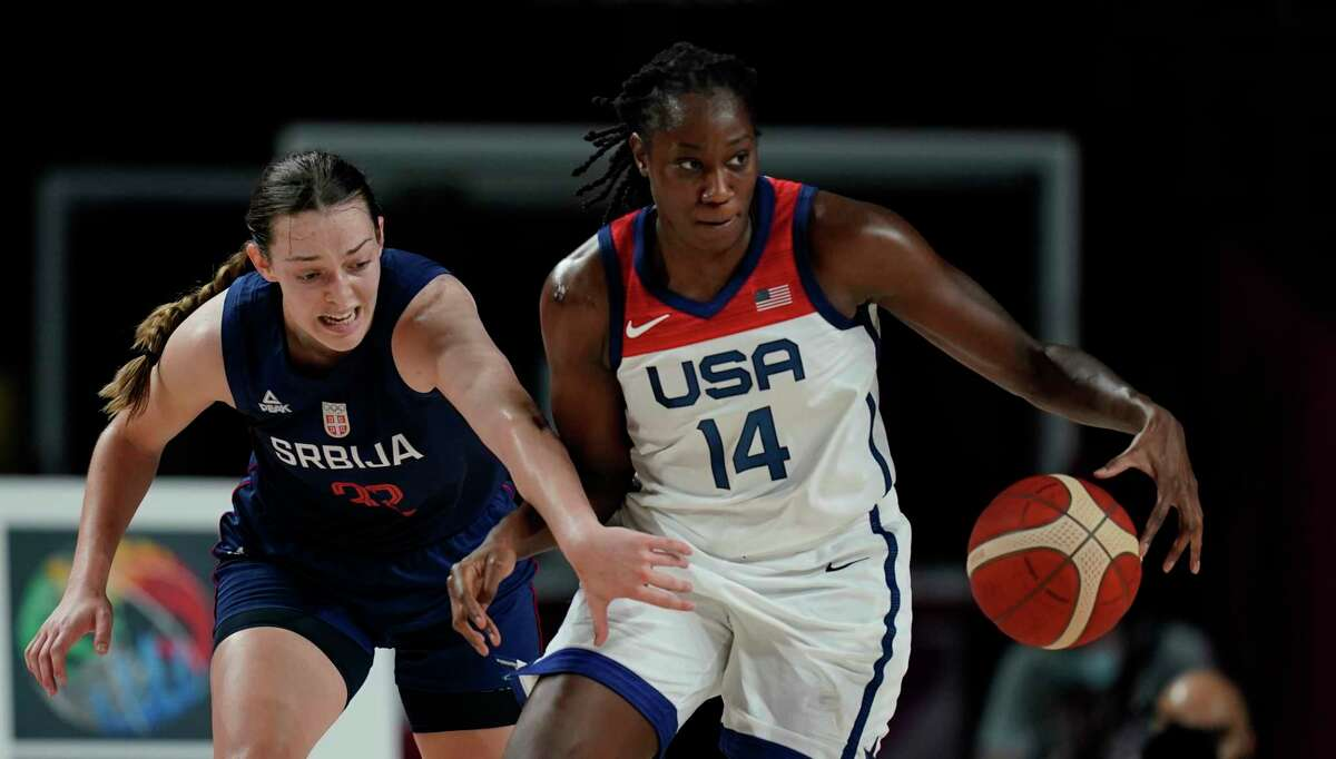 Serbia's Angela Dugalic (32), left, and United States' Tina Charles (14) chase a loose ball during women's basketball semifinal game at the 2020 Summer Olympics, Friday, Aug. 6, 2021, in Saitama, Japan. (AP Photo/Charlie Neibergall)