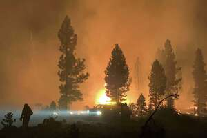 This handout photo courtesy of the U.S. Forest Service shows a firefighter and rig during night operations on the night of July 17 and early morning of July 18, 2021, at the Bootleg Fire, near Klamath Falls, Oregon.