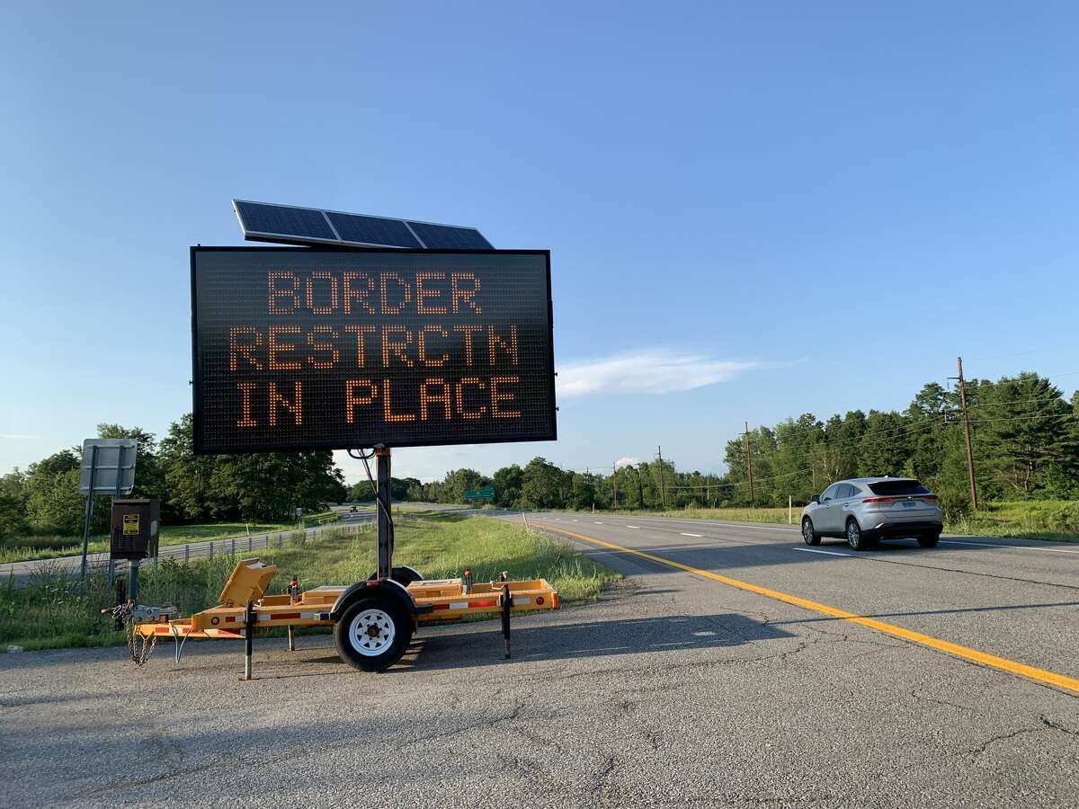 """Cars travel north towards Canada in July 2021, past a sign that reminds them """"border restrictions [are] in place."""" (Rebekah F. Ward/Times Union)"""
