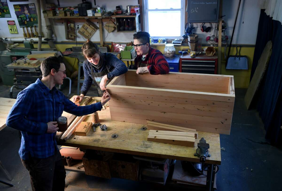 Bryan Atkins, left,and Jodi Kurtz, right, work with Marne Provost, an apprentice from Chicago, on a piece of furniture. (Photo by Jonathan Newton/The Washington Post via Getty Images)