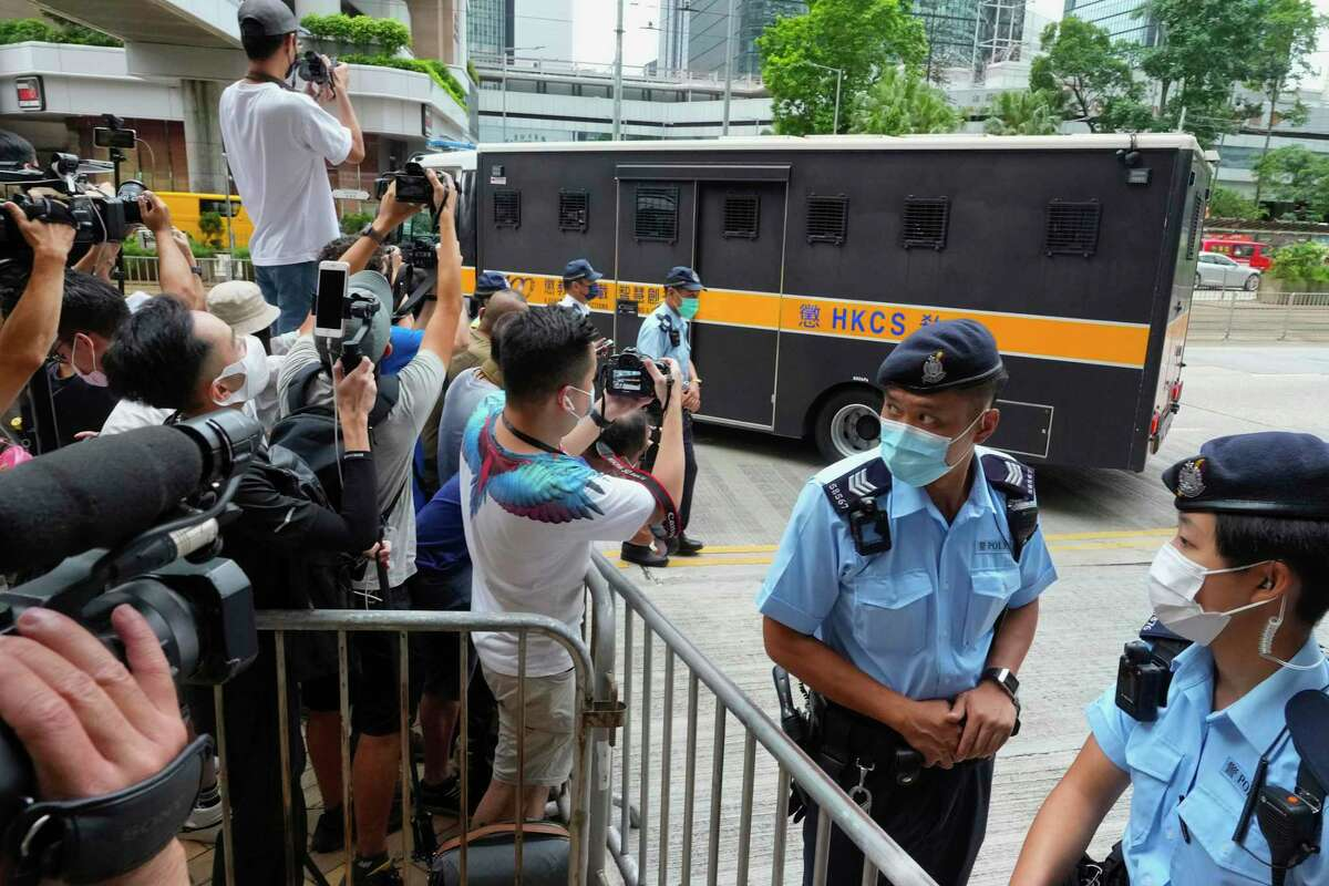 Police officers stand guard as a prison truck carrying Tong Ying-kit leaves a court Friday, July 30, 2021, after his sentencing for the violation of a security law during a 2020 protest. Tong has been sentenced to nine years in prison in the closely watched first case under Hong Kong's national security law as Beijing tightens control over the territory.