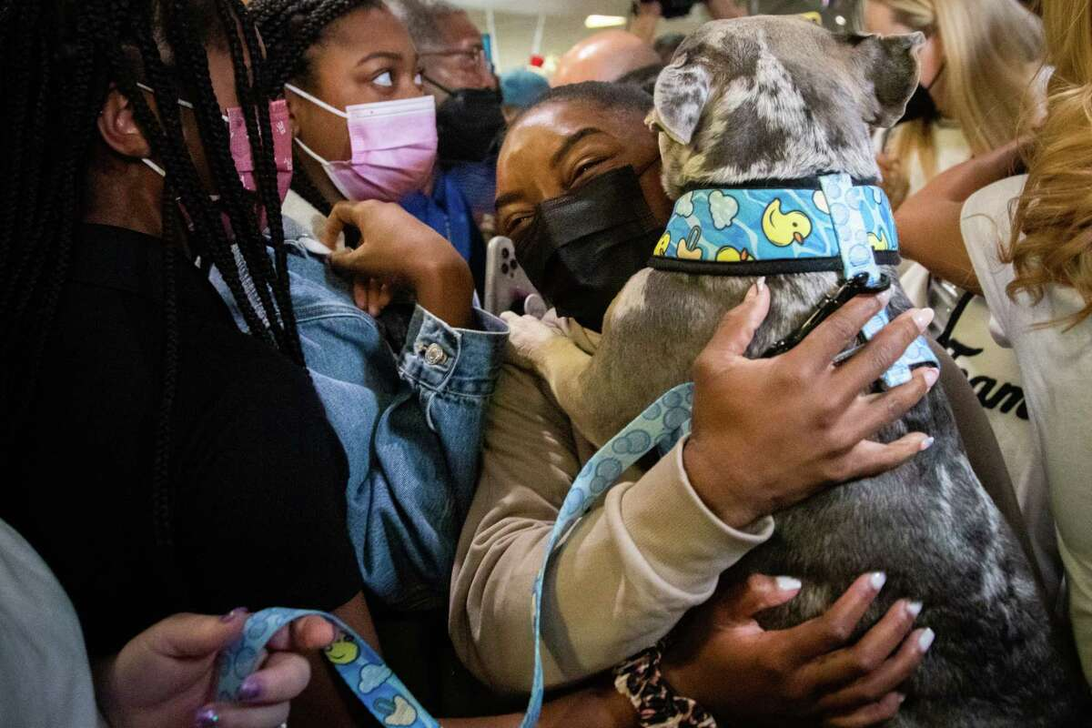 Olympic medalist Simone Biles arrives to the George Bush Intercontinental Airport baggage claim, Thursday, Aug. 5, 2021, in Houston and holds her French Bulldog Rambo after her family and many supporters arrived with her pet to the airport to receive her after she competed at the Tokyo 2020 Olympics winning two Olympic medals.