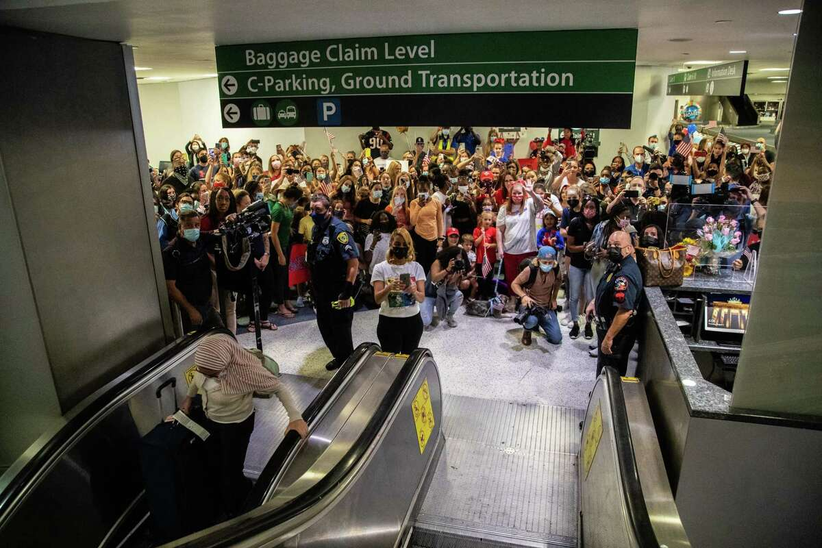 Family and supporters of Olympic medalist Simone Biles wait for her at the George Bush Intercontinental Airport baggage claim area for her to descend, Thursday, Aug. 5, 2021, in Houston.