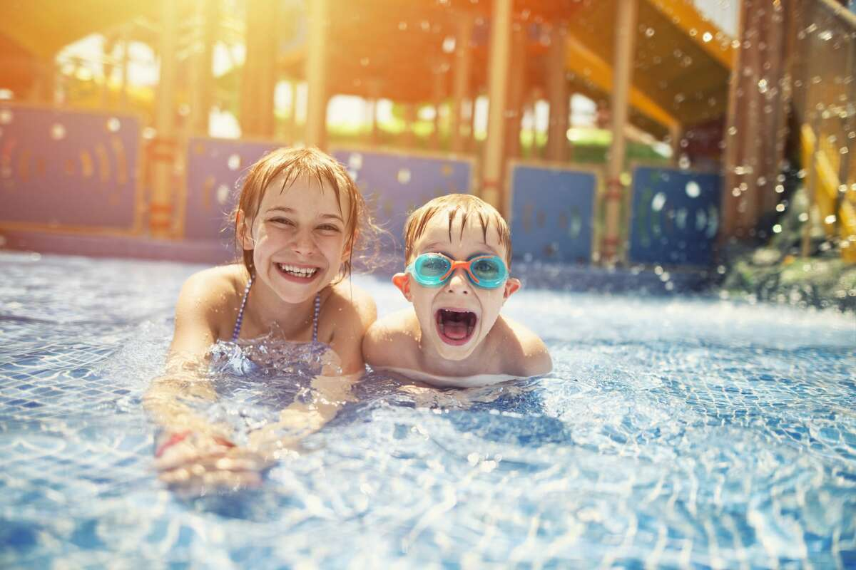 Little girl and her brother lying on front in shallow water in water park.