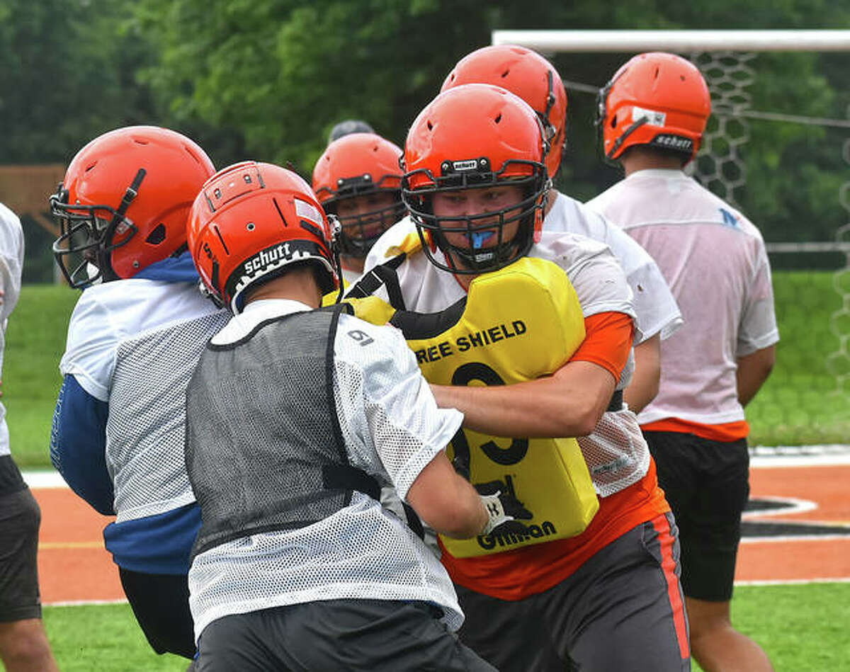 The Edwardsville Tigers run through a blocking drill during a summer practice inside the District 7 Sports Complex.