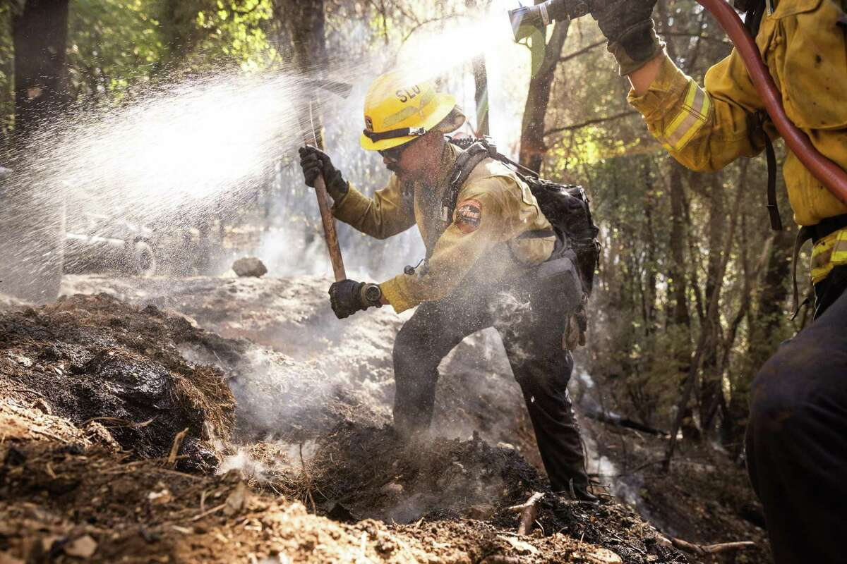 CalFire firefighters mop up the River Fire near Colfax, California area on August 5, 2021. The River Fire ignited on August 4 and burned 2,400 acres and dozens of structures.