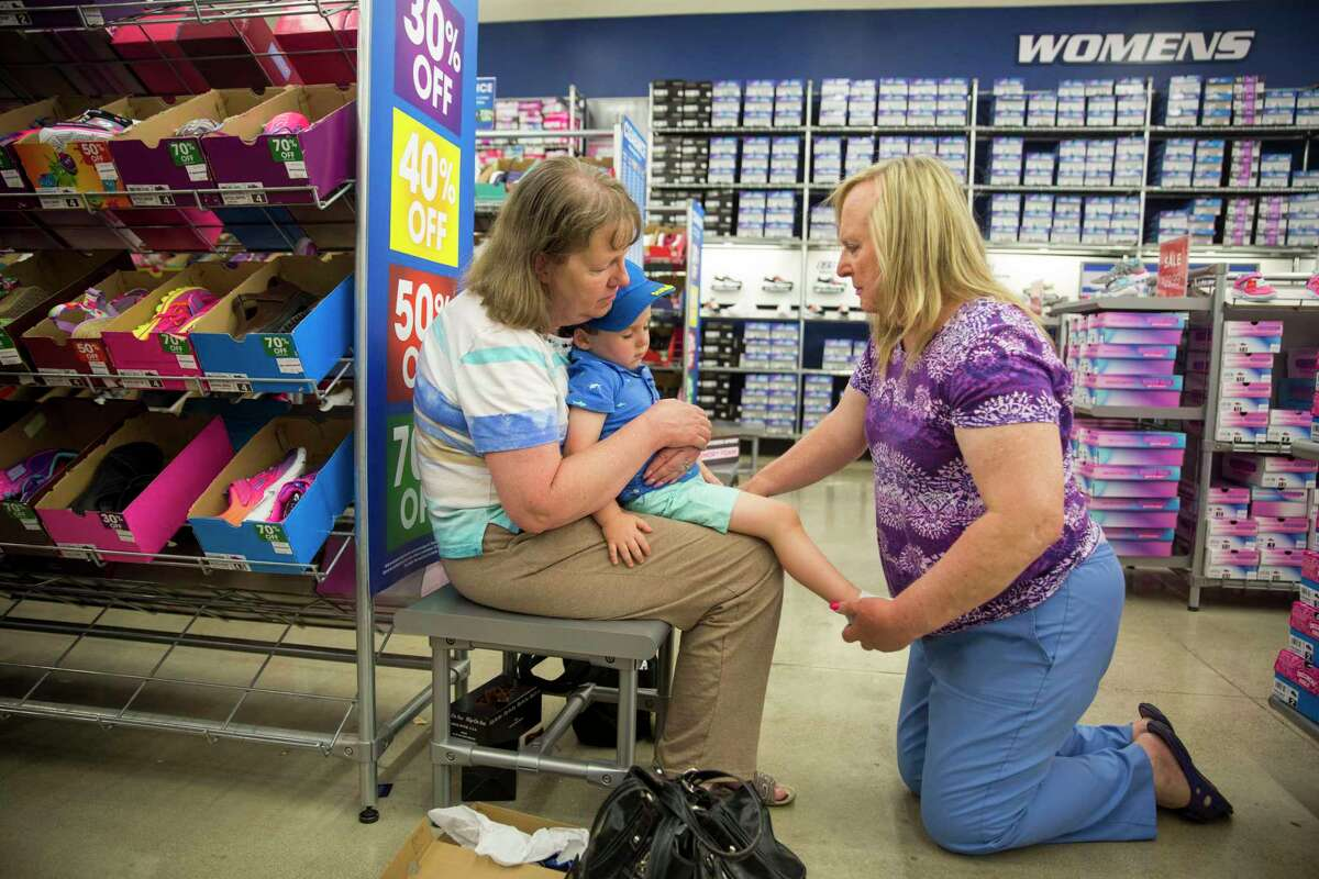 Kerry Farris holds her grandson Austin Farris as Lauryn Farris puts shoes on Austin at a Sketchers Outlet store in .