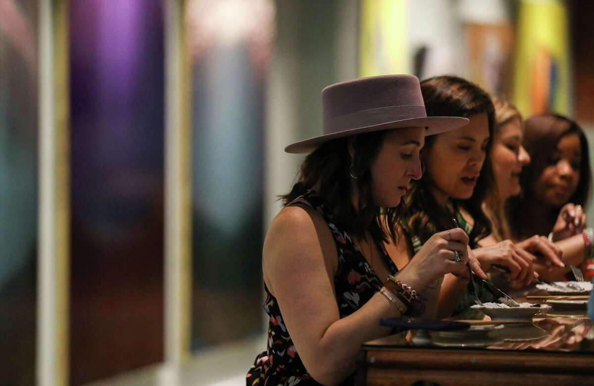 Fiona Tolunay, left, talks with Jun Wang as they eat during a dinner party Wednesday, July 28, 2021, at ReikiNa in Houston.