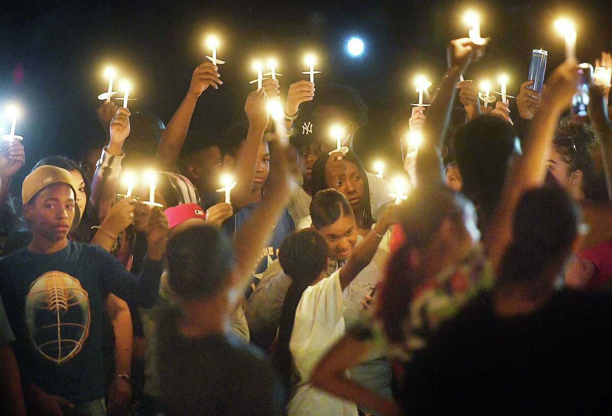 Friends and family raise candles in the air in honor of deceased 14-year-old budding football star Zyon McDuffie during a vigil in his honor at Longbrook Park in Stratford, Conn. on Thursday, August 5, 2021.