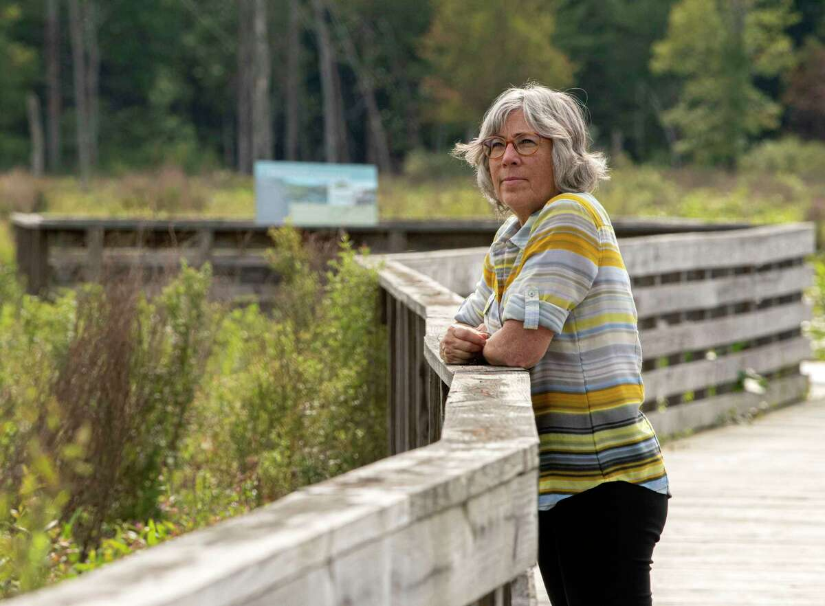 Maria Trabka who has headed Saratoga PLAN, a land conservation nonprofit, stands on a boardwalk at the Round Lake Preserve on Wednesday, Aug. 4, 2021 in Mechanicville, N.Y.